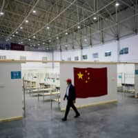 A volunteer walks inside a convention center that was used as a makeshift hospital to treat patients with the COVID-19 in Wuhan. | REUTERS