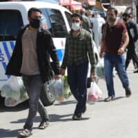Men wearing protectice facemasks carry plastic bags as they shop at the covered bazaar in the historic Ulus district, in Ankara, on April 17, 2020 as the country adopts measures to curb the spread of the COVID-19 (the novel coronavirus). - Turkish Ministry of Internal Affairs announced that the curfew will be imposed for the second time between 18-19 April in 31 provinces with metropolitan status. | AFP-JIJI