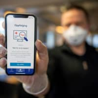 A man holds a smartphone showing a tracking and tracing app launched by the National Institute of Public Health to try to halt a return of the new coronavirus, on April 17, 2020 in Oslo. Norway, one of the first European countries to begin lifting confinement measures, is launching a smartphone tracking and tracing app that has been developed to provide health authorities a better picture of the spread of COVID-19 and tell users if they have been in contact with the disease. | AFP-JIJI