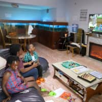 Amid the spread of the coronavirus disease, a family watches television inside their apartment in Kinshasa, Democratic Republic of Congo, on Saturday. | REUTERS
