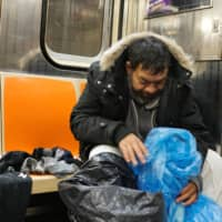Luis, who says he recently lost his job and became homeless amid the coronavirus pandemic, repacks his belongings aboard a New York subway train on April 13. | REUTERS