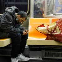 A man on a New York subway train inspects a hypodermic needle before using it. | REUTERS