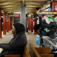 Sylver, who is homeless, sits with his belongings in a New York subway station. | REUTERS