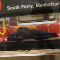 A man sleeps on a New York subway train amid the outbreak of the coronavirus in New York. | REUTERS