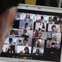 A laptop computer in Tokyo shows new employees participating in an online event on April 1. Many companies are encouraging employees to work from home, fueling an unprecedented boom in web teleconferencing. | KYODO