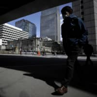 A pedestrian walks past the Bank of Japan headquarters in Tokyo. The central bank is considering further steps to improve the financing climate for struggling businesses. | BLOOMBERG
