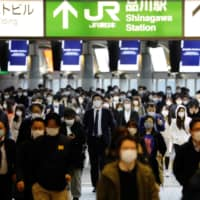 Commuters walk through Shinagawa Station in Tokyo during rush hour Monday. Many people must work at their companies despite the national state of emergency declared by the government to fight the COVID-19 outbreak. | REUTERS