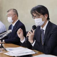Satoshi Kamayachi (second from right), a senior official at the Japan Medical Association and member of the health ministry's expert panel, attends a news conference at the ministry on Wednesday. | KYODO