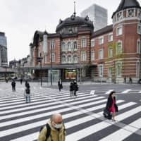 Masked people walk in front of Tokyo Station on Wednesday. | KYODO