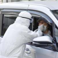 Drive-thru coronavirus testing is demonstrated in Osaka on Thursday. The Osaka Prefectural Government is looking to increase the number of tests it conducts to help contain the spread of the virus. | KYODO