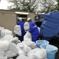 Workers pick up bags of waste in Tokyo on April 18.  | SEIICHIRO FUJII / VIA KYODO