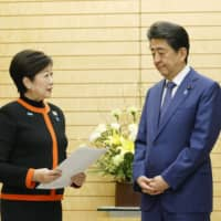 Tokyo Gov. Yuriko Koike submits requests regarding the COVID-19 outbreak control to Prime Minister Shinzo Abe at his office in Tokyo on March 26. | KYODO