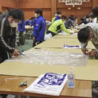 Officials of Toyonaka, Osaka Prefecture, make medical gowns out of plastic bags to offset the shortage at a local hospital on Monday. | KYODO