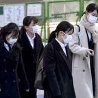 Japanese college students wear masks during visits to companies in Tokyo on March 1, as the year's job-hunting season officially began in Japan amid the ongoing spread of COVID-19. | KYODO