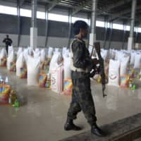 Afghan security personnel stand guard near allotments of free food donated by the Kabul Chamber of Industries and Mines for distribution to needy people during the coronavirus quarantine in Kabul on Wednesday. | AP