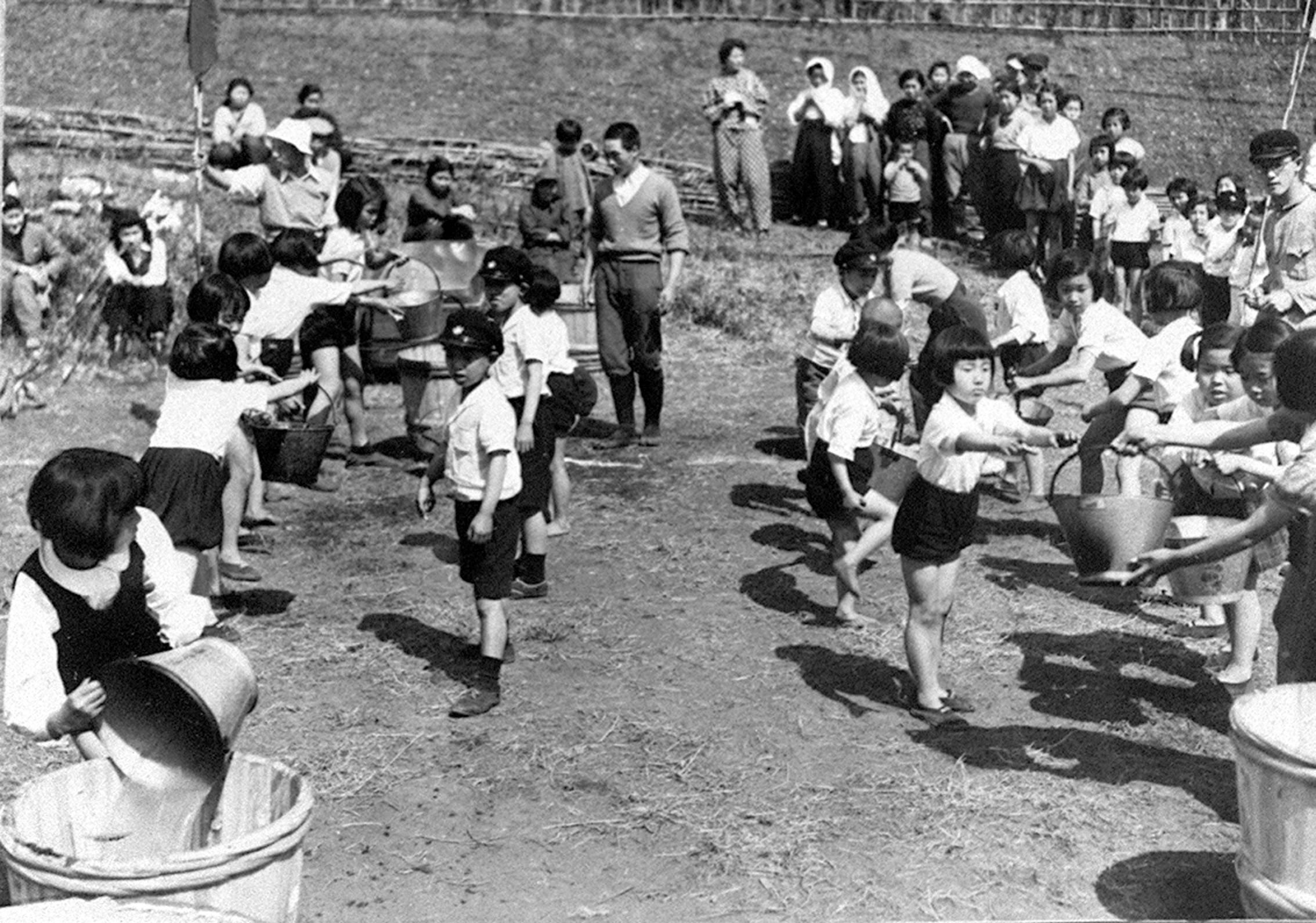 Children belonging to a neighborhood association compete by carrying buckets with water as part of a disaster prevention drill in Tokyo in April 1943. | KYODO