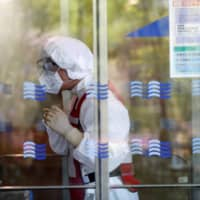 A doctor wearing an N95 mask prepares a simulation for drive-thru polymerase chain reaction (PCR) tests for the new coronavirus in Tokyo's Edogawa Ward on Wednesday. The health ministry has unveiled a list of more than 10,000 medical clinics accepting new patients for online diagnoses in an effort to curb the spread of the virus among doctors and patients. | REUTERS