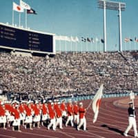 Japan's athlete delegation enters Tokyo's National Stadium during the opening ceremony of the 1964 Summer Olympics on Oct. 10, 1964. | KYODO