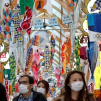 People walk under fluttering Koinobori, traditional Japanese carp-shaped windsocks that are displayed in Japan from April to early May to wish good health on children, amid the coronavirus outbreak in Tokyo on Saturday.   REUTERS