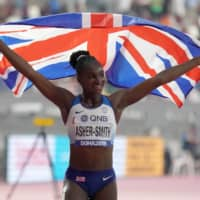 Dina Asher-Smith poses with a British flag after winning the women's 200m in a national-record 21.88 seconds during the IAAF World Athletics Championships in Doha on Oct. 2, 2019.   USA TODAY / VIA REUTERS