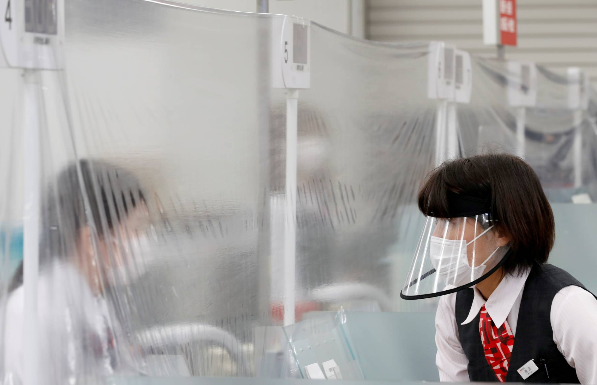 A staff member wearing a face shield talks to a bank teller at a counter where a plastic curtain is installed in order to prevent infections following the COVID-19 outbreak, at the Higashinakano branch of MUFG Bank in Tokyo on Friday. | REUTERS