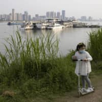 A child rides her push bike along the banks of the Yangtze River in Wuhan in China's Hubei province, on April 16. | AP