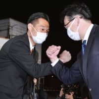 Yoichi Fukazawa (left) 'shakes hands' with a supporter after securing a seat in the Lower House by-election in Shizuoka Prefecture, on Sunday. | KYODO