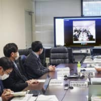 A expert panel of the health ministry meets in Tokyo's Chiyoda Ward Sunday. | KYODO