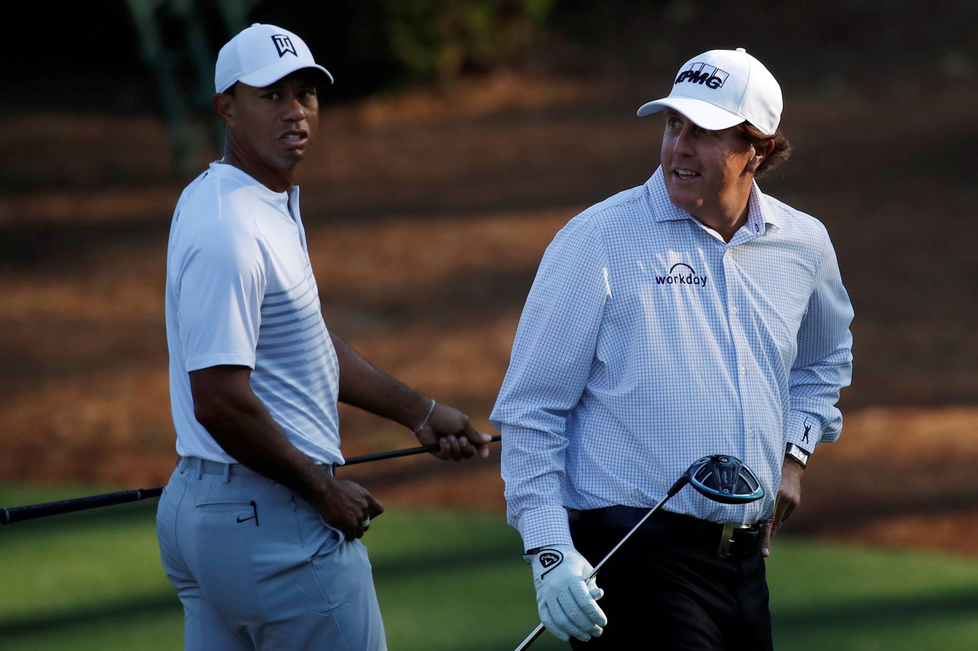 Tiger Woods (left) and Phil Mickelson walk to the 11th tee during the second day of practice for the Masters on April 3, 2018, in Augusta, Georgia. | REUTERS