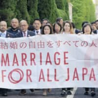 LGBT couples walk to the Tokyo District Court on April 15, 2019, for their first hearing on equality for same-sex marriages. | KYODO