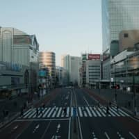 A road outside Shinjuku Station in Tokyo, usually packed on weekends, is dotted with people on Saturday amid the COVID-19 pandemic. | BLOOMBERG