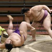 Asanoyama (right) defeats Takakeisho during the Spring Grand Sumo Tournament on March 22 in Osaka.  | KYODO
