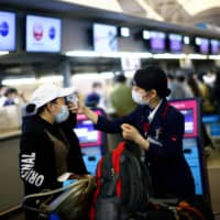A Japan Airlines employee scans the temperature to a passenger at the almost empty Kansai International Airport in Osaka on March 14. | REUTERS