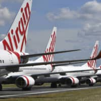 Grounded Virgin Australia aircraft are parked at Brisbane Airport in Brisbane, Australia.  | AAP IMAGE / VIA AP