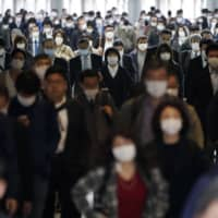 A Tokyo train station passageway is crowded with commuters during rush hour on Monday. | AP