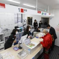 The Japan Post Holdings Co. group has revoked certificates to sell insurance of 75 post office workers, while reprimanding two others, for their improper sales of insurance products. | KYODO