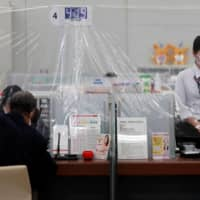 An employee at a MUFG Bank branch in central Tokyo on Friday stands behind a plastic curtain installed to prevent coronavirus infections. | REUTERS
