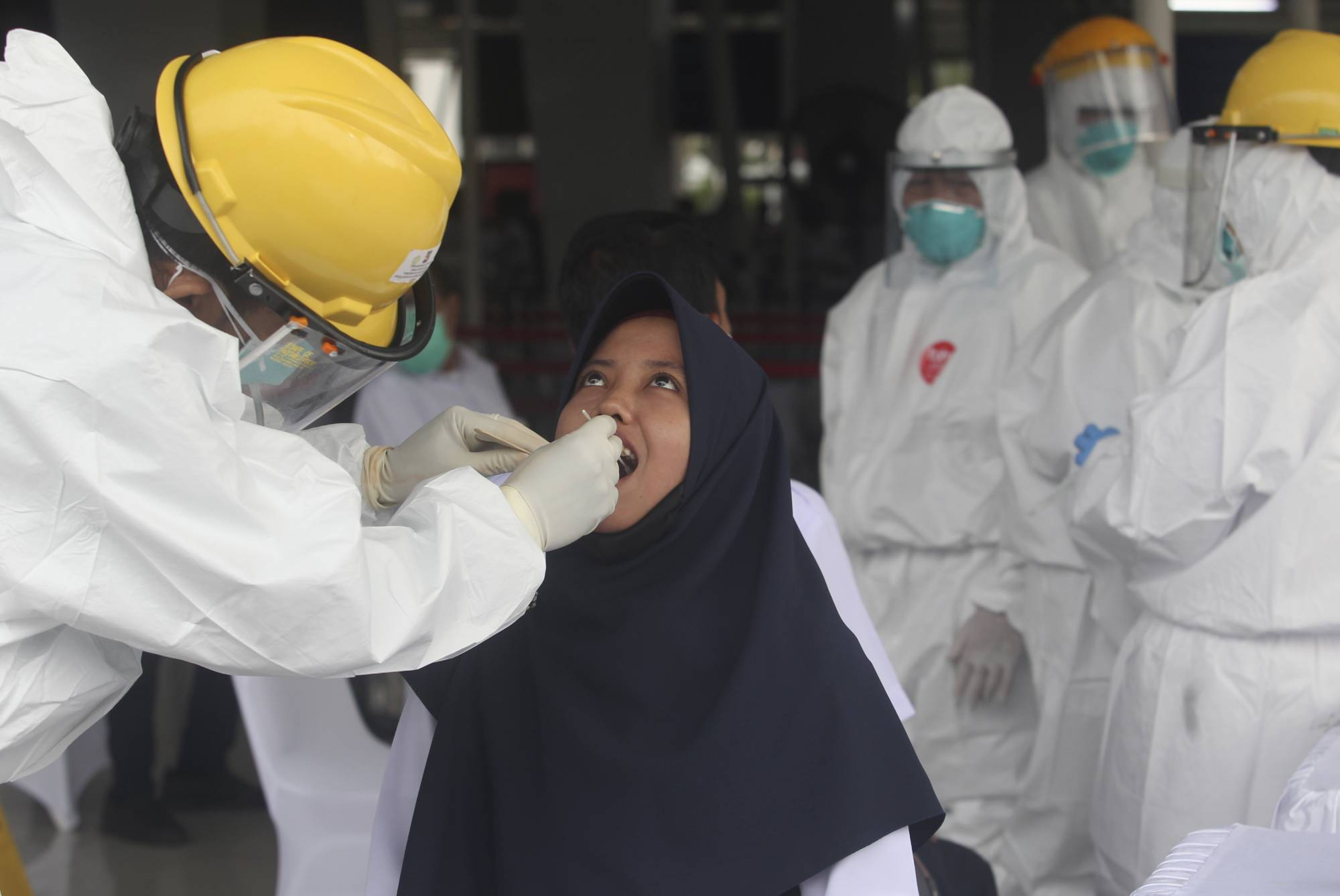 A health worker conducts a test for the new coronavirus on a woman in Bogor, Indonesia, on Monday.   AP