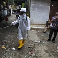 A worker sprays disinfectant in an attempt to curb the spread of the coronavirus in a slum area in Jakarta last Wednesday.    AP