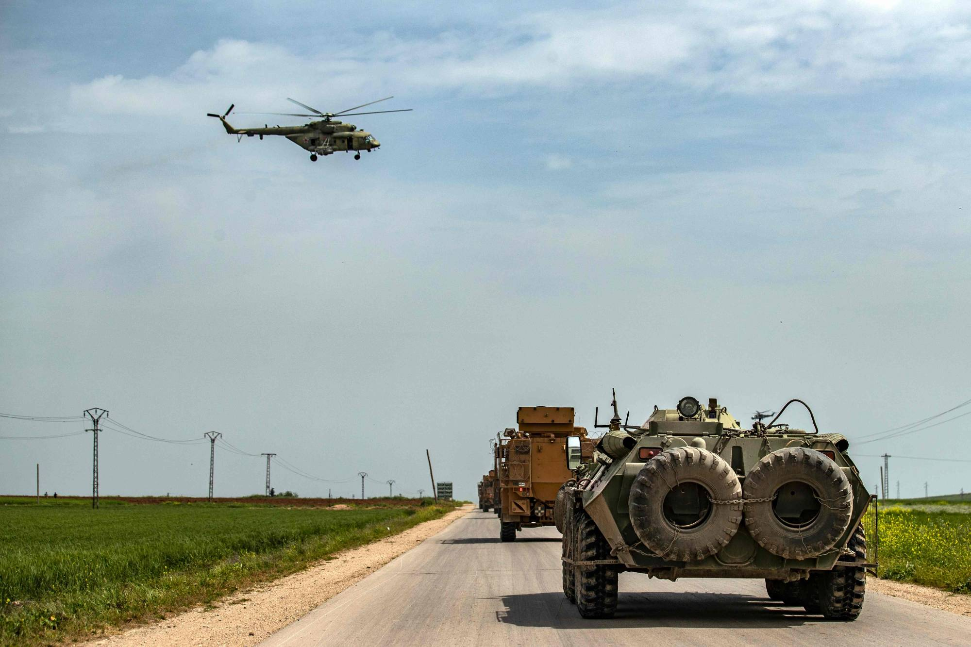 A Russian Air Force Mil Mi-28 military helicopter flies over Turkish and Russian military vehicles taking part in a joint Turkish-Russian patrol outside the Syrian town of Darbasiyah near the Turkish border in the province of Hasakah, on April 22. | AFP-JIJI