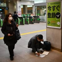 Travelers are seen wearing face masks at a train station in Tokyo on Tuesday. | AFP-JIJI