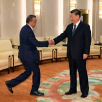 Tedros Adhanom, director general of the World Health Organization, shakes hands with Chinese President Xi jinping before a meeting in Beijing on Jan. 28. | REUTERS