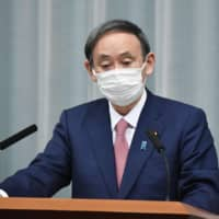 Chief Cabinet Secretary Yoshihide Suga attends a news conference on Monday in Tokyo.  | KYODO