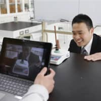 Teachers at an elementary school in Minoo, Osaka Prefecture, record a video for a science class on April 20. | KYODO