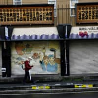 A man wearing a protective face mask walks past closed shops at Tsukiji market in Tokyo on Tuesday. | REUTERS