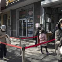 Customers wearing protective masks use social distancing markers at the entrance to a store selling steamed buns in Beijing on April 23. | BLOOMBERG