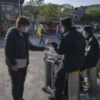 A security official checks the temperature of a pedestrian wearing a protective mask at a checkpoint in the Dashilan area of Beijing on April 23.  | BLOOMBERG