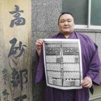 Newly promoted ozeki Asanoyama holds banzuke for the Summer Grand Sumo Tournament on Monday in front of his Takasago stable in Tokyo. Banzuke was issued as scheduled but whether the Summer Basho will be held is still unclear. | KYODO
