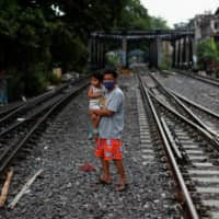 A man wearing a protective mask holds a child as he crosses the tracks in a slum in Bangkok on Monday. | REUTERS