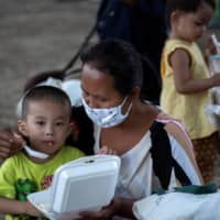 A mother affected by government measures to stop the spread of COVID-19 feeds her son after receiving free meals at a park in Bangkok. REUTERS | REUTERS